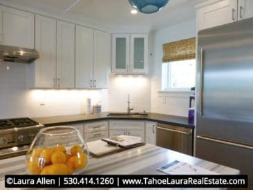 View of new beach style kitchen with free standing island, white cabinets stainless steel appliances and gray marble solid surface counter tops.