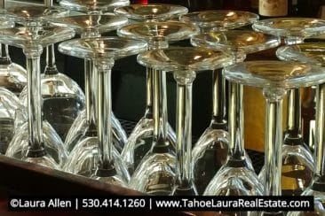 Picture is of three wine glasses that are lined up in a row on a wooden table top. Each glass has a different wine in it. The first is a deeper yellow color, the middle has a rose colored wine, and the third wine glass has a light yellow-greenish tint wine in it. At the bottom is Laura Allens' name and contact information 530-414-1260 and website www.TahoeLauraRealEstate.com